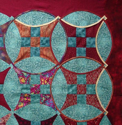Closeup of Sonya's red and turquoise quilt top.