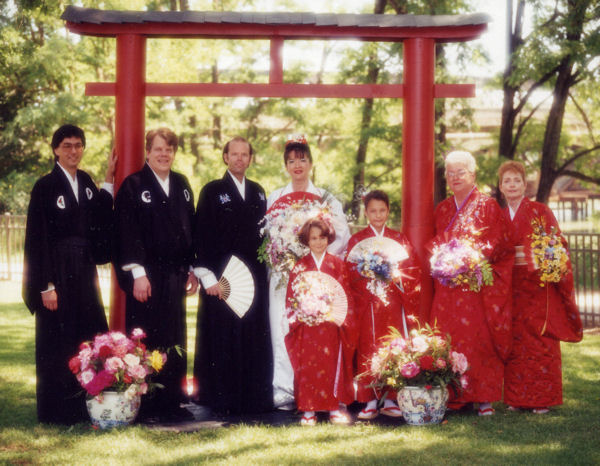 Full wedding party in front of the Torii Gate.